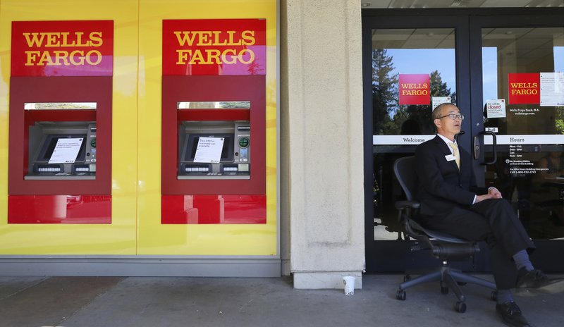 Personal banker Joce Richmond sits outside of a Wells Fargo branch to help customers during the power shutdown in Santa Rosa, Calif., Thursday, Oct. 10, 2019. The branch was allowing customers to enter one at a time and offered limited transactions. More than 1.5 million people in Northern California were without power Thursday, most for a second day, after the state's biggest utility shut off electricity to many areas to prevent its equipment from sparking wildfires as strong winds sweep through the region. (Christopher Chung/The Press Democrat via AP)