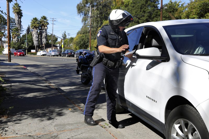 Santa Rosa Police Officer John Meteyer stops a driver for failing to stop at an intersection where the traffic lights are out along Fourth Street at Bryden Lane in Santa Rosa, Calif., Thursday, Oct. 10, 2019. More than 1.5 million people in Northern California were without power Thursday, most for a second day, after the state's biggest utility shut off electricity to many areas to prevent its equipment from sparking wildfires as strong winds sweep through the region. (Christopher Chung/The Press Democrat via AP)