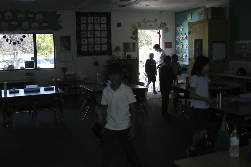 Students walk back into Janet Ghani's 3rd grade class after a recess at Williams Elementary in San Jose, Calif., Thursday, Oct. 10, 2019. Students, faculty and staff continued on with classes relying on sunlight pouring in from windows after a Pacific Gas and Electric planned power shutdown turned out the lights. More than 1.5 million people in Northern California were in the dark Thursday, most for a second day, after the state's biggest utility shut off electricity to many areas to prevent its equipment from sparking wildfires as strong winds sweep through the region. (Anda Chu/San Jose Mercury News via AP)