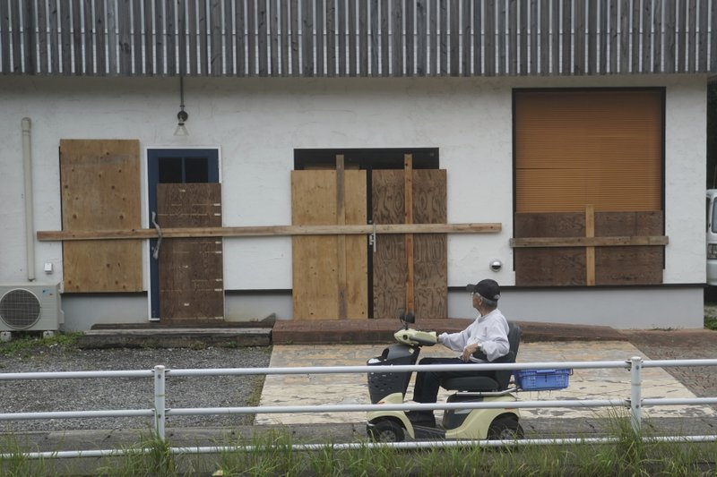 A man looks at a shop, protected by wood boards, as Typhoon Hagibis approaches in town of Kiho, Mie Prefecture, Japan Friday, Oct. 11, 2019. A powerful typhoon was forecast to bring 2 feet of rain and damaging winds to the Tokyo area this weekend, and Japan's government warned people Friday to stockpile supplies and evacuate before it's too dangerous. (AP Photo/Toru Hanai)