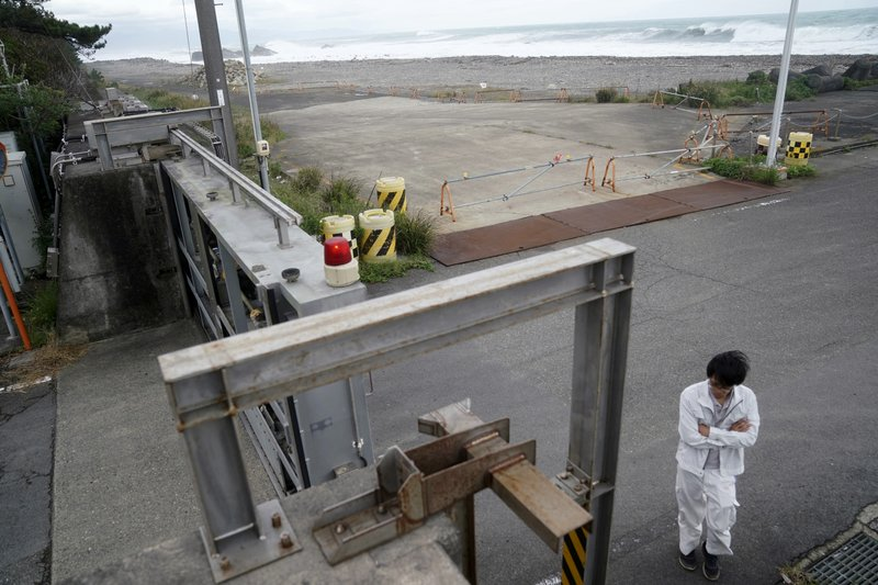 A Kiho town official prepares to close a door of a coastal levee as Typhoon Hagibis approaches at a port in town of Kiho, Mie prefecture, central Japan Friday, Oct. 11, 2019. A powerful typhoon is advancing toward the Tokyo area, where torrential rains are expected this weekend. (AP Photo/Toru Hanai)