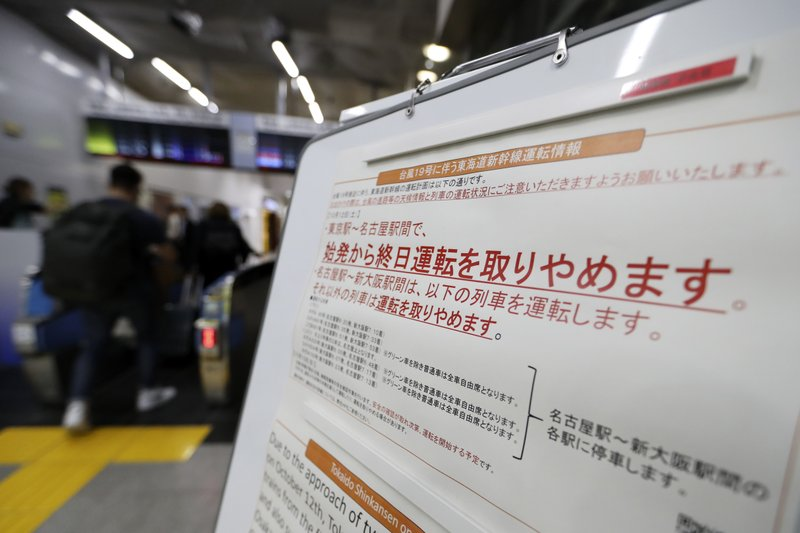A notice paper on suspending operations of the Shinkansen or bullet train on Oct. 12-13 due to Typhoon Hagibis, is posted at Tokyo Station in Tokyo Friday, Oct. 11, 2019. Japan's weather agency is warning a powerful typhoon may bring torrential rains to central Japan over the weekend. (AP Photo/Eugene Hoshiko)
