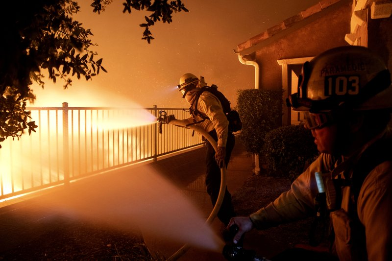 In this Thursday, Oct. 10, 2019 photo, Los Angeles City firefighters battle the Saddleridge fire near homes in Sylmar, Calif. (AP Photo/Michael Owen Baker)