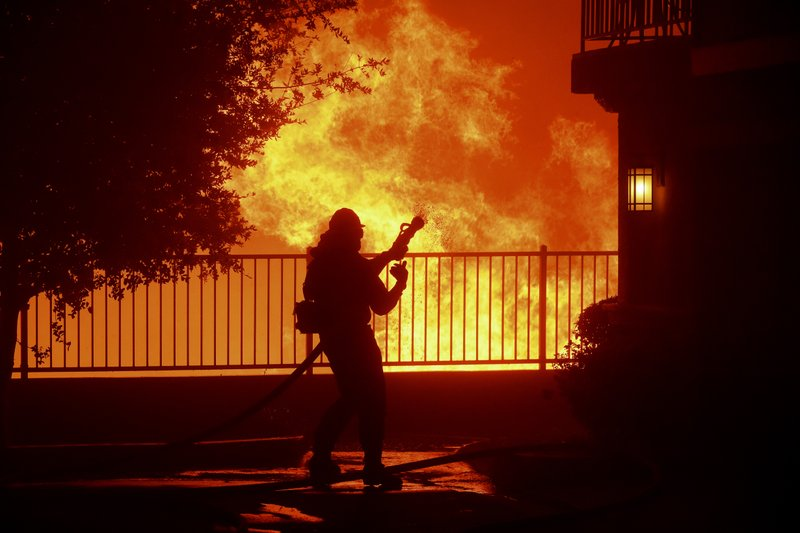 In this Thursday, Oct. 10, 2019 photo, a firefighter waits for water as the Saddleridge fire flares up near homes in Sylmar, Calif. (AP Photo/Michael Owen Baker)