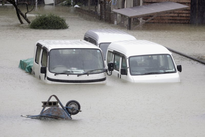 Cars sit submerged in water in the residential area hit by Typhoon Hagibis, in Ise, central Japan Saturday, Oct. 12, 2019. A heavy downpour and strong winds pounded Tokyo and surrounding areas on Saturday as a powerful typhoon forecast as the worst in six decades approached landfall, with streets and train stations deserted and shops shuttered.(Kyodo News via AP)