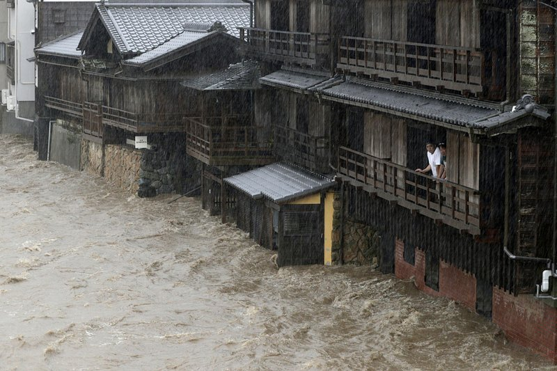 People watch the Isuzu River swollen by Typhoon Hagibis, in Ise, central Japan Saturday, Oct. 12, 2019. Tokyo and surrounding areas braced for a powerful typhoon forecast as the worst in six decades, with streets and trains stations unusually quiet Saturday as rain poured over the city. (Kyodo News via AP)