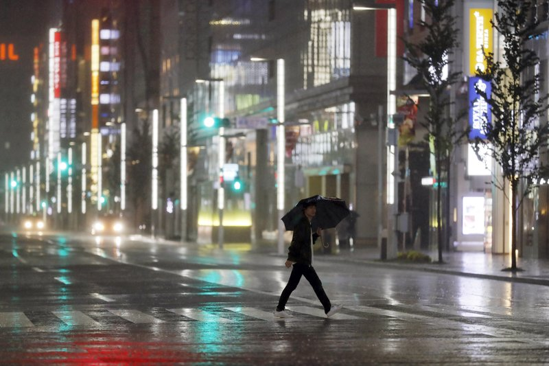 A man walks a pedestrian crossing at Ginza shopping district in the pouring rain due to Typhoon Hagibis in Tokyo Saturday, Oct. 12, 2019. A heavy downpour and strong winds pounded Tokyo and surrounding areas on Saturday as a powerful typhoon forecast as the worst in six decades approached landfall, with streets and train stations deserted and shops shuttered. (AP Photo/Eugene Hoshiko)