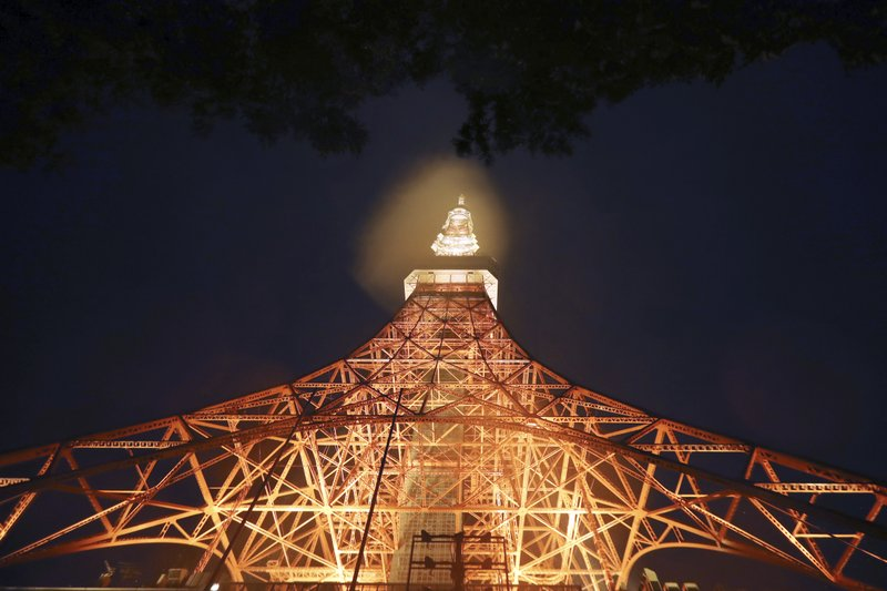 Tokyo Tower is lit in the pouring rain due to Typhoon Hagibis in Tokyo Saturday, Oct. 12, 2019. A heavy downpour and strong winds pounded Tokyo and surrounding areas on Saturday as a powerful typhoon forecast as the worst in six decades approached landfall, with streets and train stations deserted and shops shuttered. (AP Photo/Eugene Hoshiko)