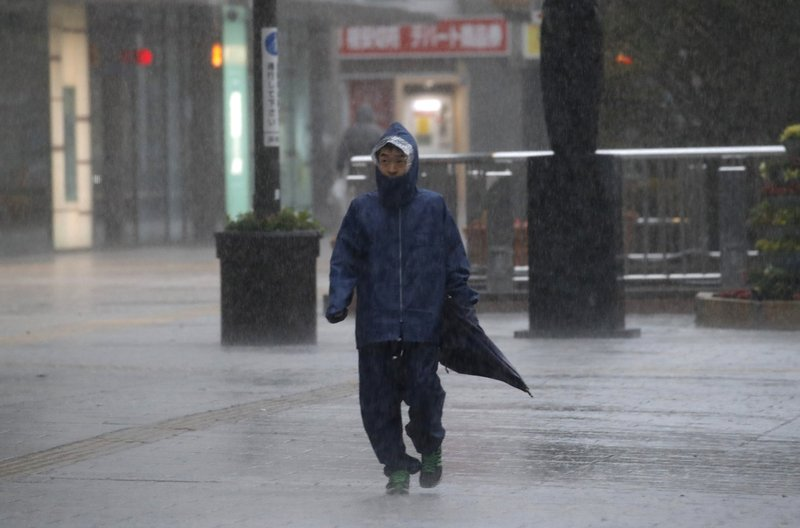 A man walks in heavy rain in Hamamatsu, central Japan, Saturday, Oct. 12, 2019. A heavy downpour and strong winds pounded Tokyo and surrounding areas on Saturday as a powerful typhoon forecast as the worst in six decades approached landfall, with streets and train stations deserted and shops shuttered. (AP Photo/Christophe Ena)
