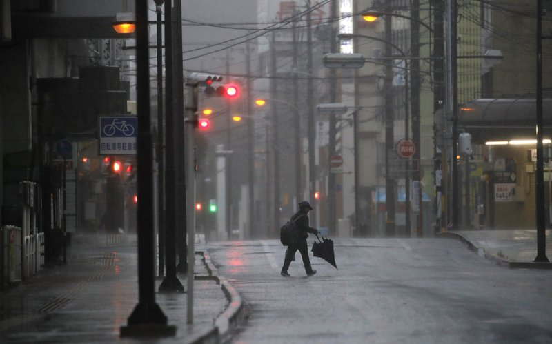 A woman crosses the road in Hamamatsu, central Japan, Saturday, Oct. 12, 2019. A heavy downpour and strong winds pounded Tokyo and surrounding areas on Saturday as a powerful typhoon forecast as the worst in six decades approached landfall, with streets and train stations deserted and shops shuttered. (AP Photo/Christophe Ena)