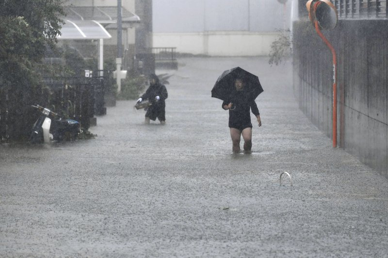 People walk through a flooded street affected by Typhoon Hagibis, in Shizuoka, central Japan Saturday, Oct. 12, 2019. Tokyo and surrounding areas braced for a powerful typhoon forecast as the worst in six decades, with streets and trains stations unusually quiet Saturday as rain poured over the city. (Kyodo News via AP)