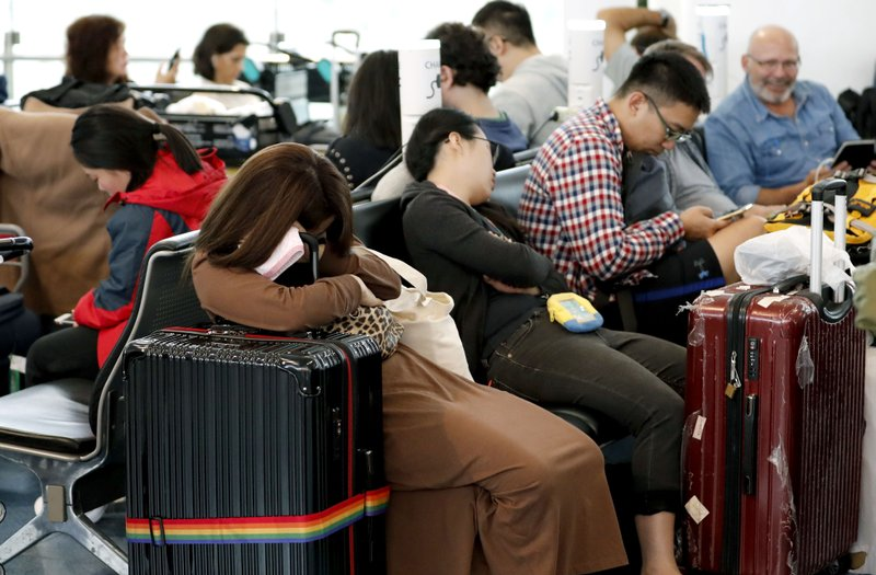 Passengers rest as their flights were cancelled because of Typhoon Hagibis, at Haneda Airport in Tokyo, Saturday, Oct. 12, 2019. Tokyo and surrounding areas braced for a powerful typhoon forecast as the worst in six decades, with streets and trains stations unusually quiet Saturday as rain poured over the city. (Kyodo News via AP)