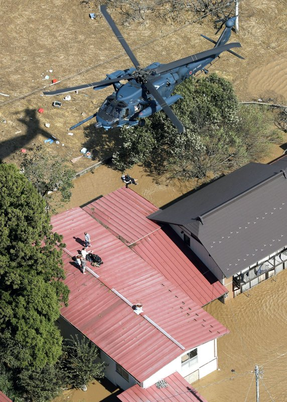 Stranded residents are rescued by a helicopter as the town is flooded by typhoon Hagibis, in Marumori, Miyagi prefecture, northern Japan, Sunday, Oct. 13, 2019. Rescue efforts for people stranded in flooded areas are in full force after a powerful typhoon dashed heavy rainfall and winds through a widespread area of Japan, including Tokyo.(Kyodo News via AP)