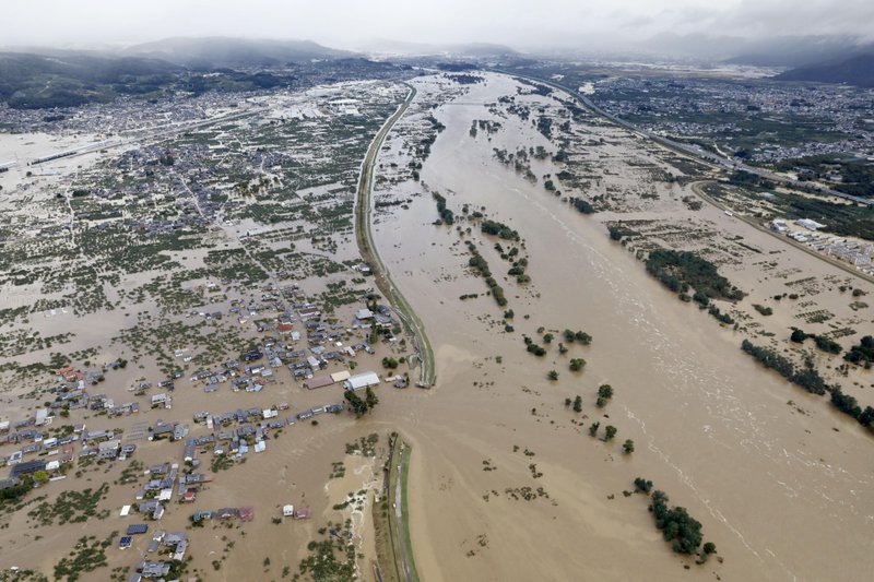 Residential area, left, are submerged in muddy waters after an embankment of the Chikuma River broke because of Typhoon Hagibis, in Nagano, central Japan, Sunday, Oct. 13, 2019. Rescue efforts for people stranded in flooded areas are in full force after a powerful typhoon dashed heavy rainfall and winds through a widespread area of Japan, including Tokyo.(Yohei Kanasashi/Kyodo News via AP)