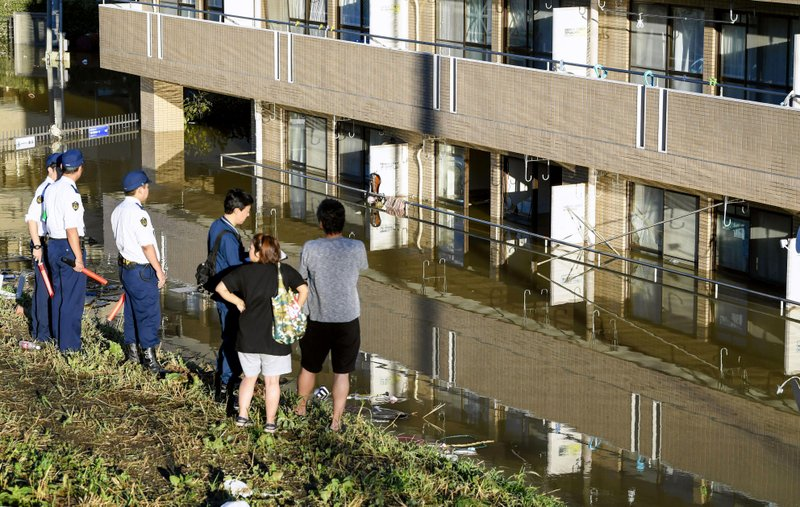 People look at an apartment building with its first floor under water in the residential area hit by Typhoon Hagibis, in Kawasaki, near Tokyo, Sunday, Oct. 13, 2019. Rescue efforts for people stranded in flooded areas are in full force after a powerful typhoon dashed heavy rainfall and winds through a widespread area of Japan, including Tokyo.(Kyodo News via AP)