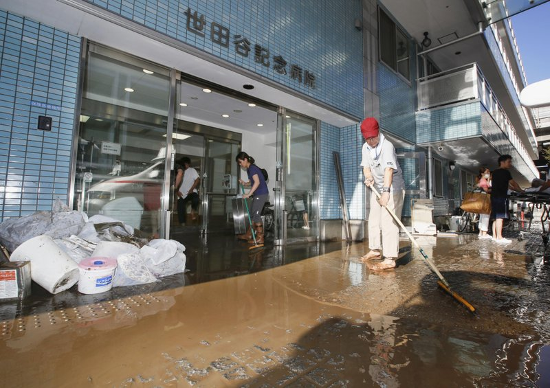 People clean a flooded hospital hit by Typhoon Hagibis, in Tokyo Sunday, Oct. 13, 2019. Rescue efforts for people stranded in flooded areas are in full force after a powerful typhoon dashed heavy rainfall and winds through a widespread area of Japan, including Tokyo.(Kyodo News via AP)