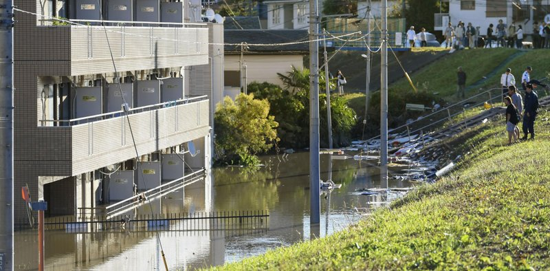 People look at a apartment building with its first floor under water in the residential area hit by Typhoon Hagibis, in Kawasaki, near Tokyo, Sunday, Oct. 13, 2019. Rescue efforts for people stranded in flooded areas are in full force after a powerful typhoon dashed heavy rainfall and winds through a widespread area of Japan, including Tokyo.(Kyodo News via AP)