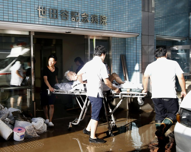 An injured people on stretcher is carried out of a flooded hospital in Tokyo Sunday, Oct. 13, 2019. Rescue efforts for people stranded in flooded areas are in full force after a powerful typhoon dashed heavy rainfall and winds through a widespread area of Japan, including Tokyo.(Kyodo News via AP)