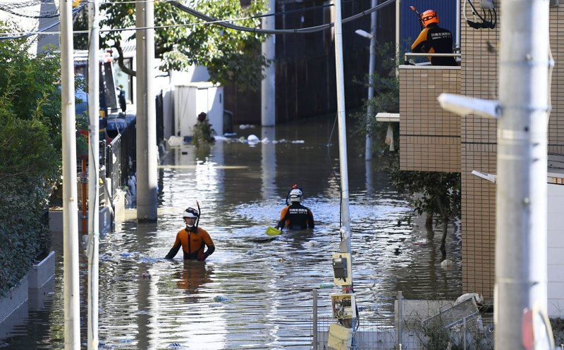 Firefighters make their way through flooded street as Typhoon Hagibis hit the area in Kawasaki, near Tokyo,  Japan, Sunday, Oct. 13, 2019. Rescue efforts for people stranded in flooded areas are in full force after a powerful typhoon dashed heavy rainfall and winds through a widespread area of Japan, including Tokyo.(Ren Onuma/Kyodo News via AP)