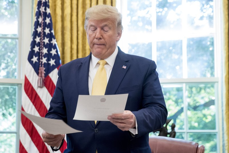 President Donald Trump holds a letter presented to him by Chinese Vice Premier Liu He, left, in the Oval Office of the White House in Washington, Friday, Oct. 11, 2019. (AP Photo/Andrew Harnik)
