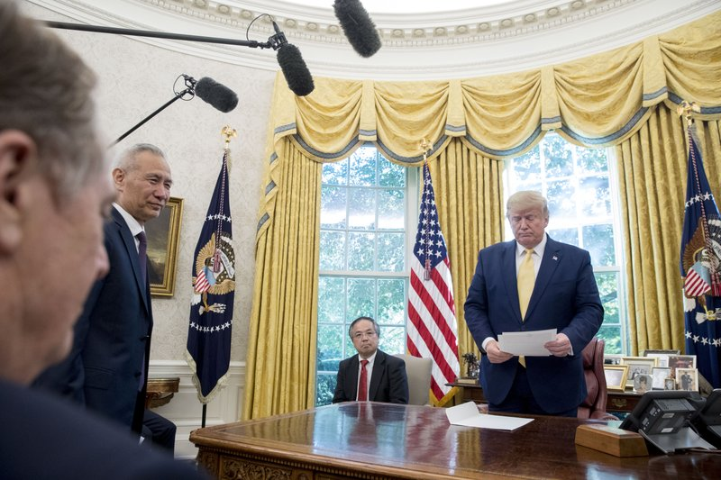 President Donald Trump holds a letter presented to him by Chinese Vice Premier Liu He, second from left, in the Oval Office of the White House in Washington, Friday, Oct. 11, 2019. Also pictured is U.S. Trade Representative Robert Lighthizer, left. (AP Photo/Andrew Harnik)