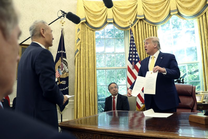 President Donald Trump holds a letter presented to him by Chinese Vice Premier Liu He in the Oval Office of the White House in Washington, Friday, Oct. 11, 2019. (AP Photo/Andrew Harnik)