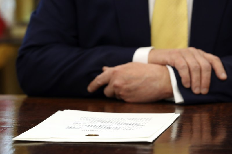 A letter presented to President Donald Trump by Chinese Vice Premier Liu He on the desk in front of Trump in the Oval Office of the White House in Washington, Friday, Oct. 11, 2019. (AP Photo/Andrew Harnik)