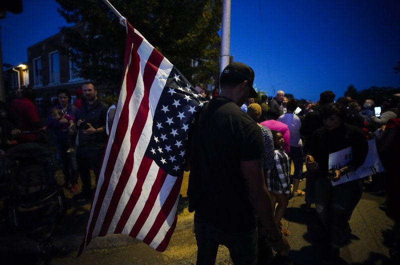 A large crowd of protesters, including a man carrying an upside-down American flag, gather outside the house where Atatiana Jefferson was shot Saturday and killed by police, during a community vigil for Jefferson on Sunday, Oct. 13, 2019, in Fort Worth, Texas. A white police officer who killed the black woman inside her Texas home while responding to a neighbor's call about an open front door