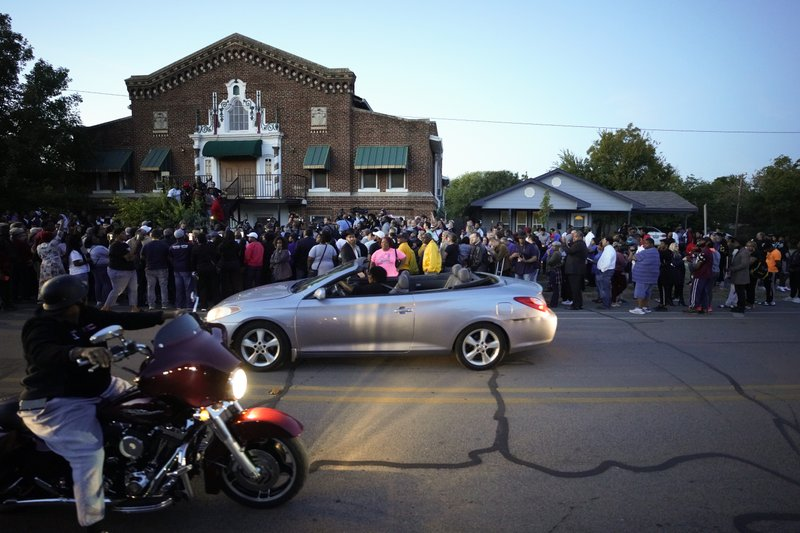A large crowd of protesters gather outside the house, right, where Atatiana Jefferson was shot Saturday and killed by police, during a community vigil for Jefferson on Sunday, Oct. 13, 2019, in Fort Worth, Texas. A white police officer who killed the black woman inside her Texas home while responding to a neighbor's call about an open front door