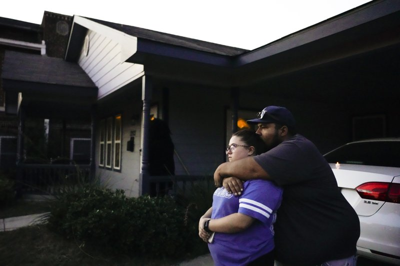 Destinie and Floriberto Bartolo mourn for their friend Atatiana Jefferson, who they say they have known since high school, outside the house where Jefferson was shot and killed by a police officer, during a community vigil for Jefferson on Sunday, Oct. 13, 2019, in Fort Worth, Texas. A white police officer who killed the black woman inside her Texas home while responding to a neighbor's call about an open front door