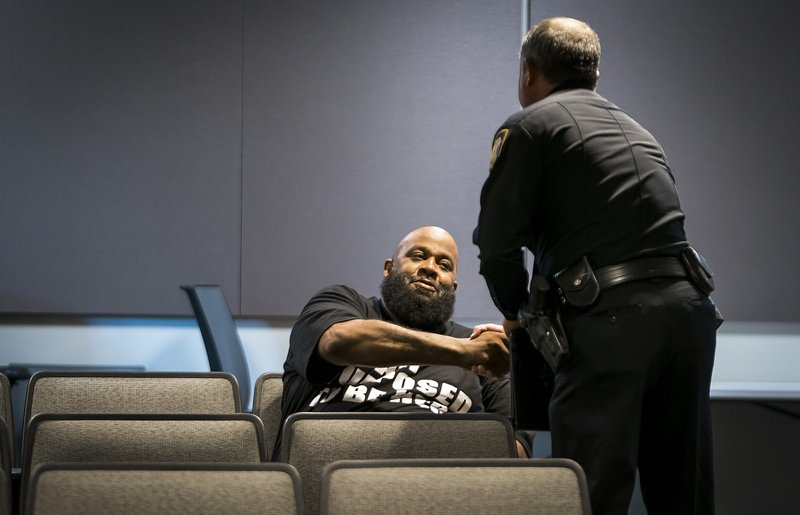 Fort Worth Police Lt. Brandon O'Neil shakes hands with Roger Foggle after addressing a news conference regarding the shooting of Atatiana Jefferson at the Bob Bolen Public Safety Complex on Sunday, Oct. 13, 2019, in Fort Worth, Texas. A white police officer who killed the black woman inside her Texas home while responding to a neighbor's call about an open front door