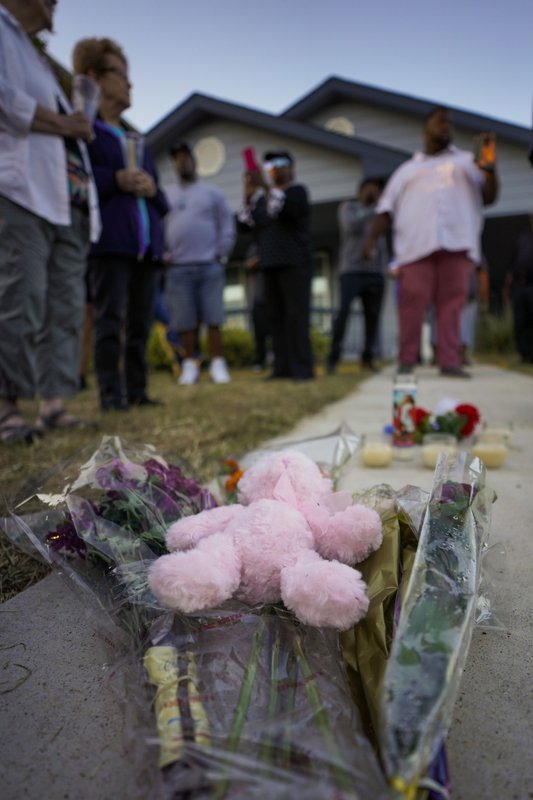 Protesters left flowers outside the house, in the background, where Atatiana Jefferson was shot and killed, durin a community vigil for Atatiana Jefferson on Sunday, Oct. 13, 2019, in Fort Worth, Texas. A white police officer who killed the black woman inside her Texas home while responding to a neighbor's call about an open front door