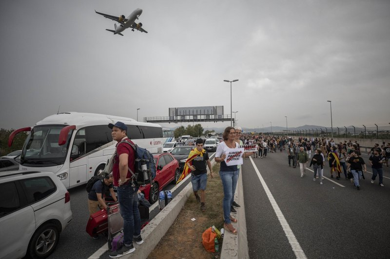 Protesters block the roads leading to El Prat airport, outskirts of Barcelona, Spain, Monday, Oct. 14, 2019. Spain's Supreme Court on Monday sentenced 12 prominent former Catalan politicians and activists to lengthly prison terms for their roles in a 2017 bid to gain Catalonia's independence, sparking protests across the wealthy Spanish region. The banners in the center read in Catalan