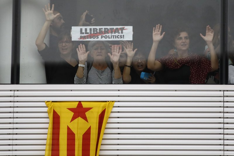Protestors stand behind a banner reading in Catalan,