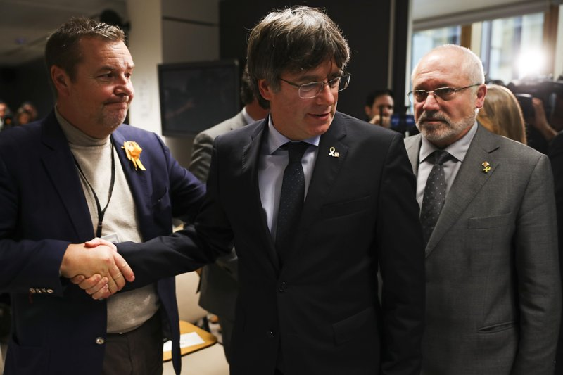 Catalonia's former regional president Carles Puigdemont, center, arrives to give a statement in Brussels, Monday, Oct. 14, 2019. A dozen Catalan politicians and activists have been convicted on charges of sedition, misuse of public funds and disobedience for their role in an illegal and failed secession attempt for the northeastern region of Spain in 2017. (AP Photo/Francisco Seco)
