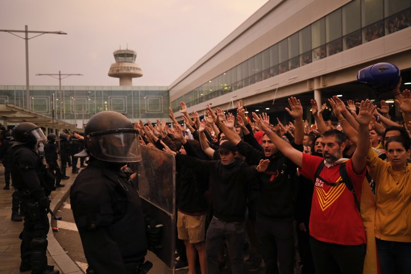 Protestors raise their arms in front of a line of riot policemen outside El Prat airport in Barcelona, Spain, Monday, Oct. 14, 2019. Riot police have charged at protesters outside Barcelona's airport after the Supreme Court sentenced 12 prominent Catalan separatists to lengthy prison terms for their roles in a 2017 push for the wealthy Spanish region's independence. (AP Photo/Emilio Morenatti)
