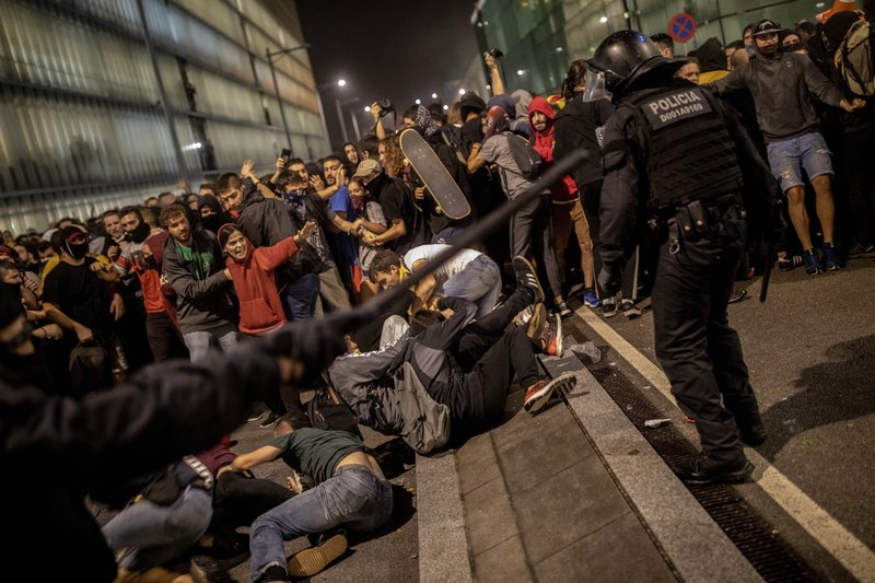 Police clash with protesters during a demonstration at El Prat airport, outskirts of Barcelona, Spain, Monday, Oct. 14, 2019. Spain's Supreme Court on Monday sentenced 12 prominent former Catalan politicians and activists to lengthly prison terms for their roles in a 2017 bid to gain Catalonia's independence, sparking protests across the wealthy Spanish region. (AP Photo/Bernat Armangue)
