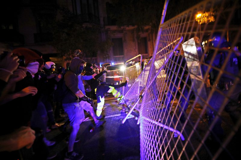 Protestors kick down a fence outside the Spanish Government Office in Barcelona, Spain, Tuesday, Oct. 15, 2019. Spain's Supreme Court on Monday convicted 12 former Catalan politicians and activists for their roles in a secession bid in 2017, a ruling that immediately inflamed independence supporters in the wealthy northeastern region. (AP Photo/Emilio Morenatti)