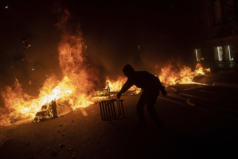 A protester drags a chair next to a burning barricade during clashes with police in Barcelona, Spain, Tuesday, Oct. 15, 2019. Spain's Supreme Court on Monday convicted 12 former Catalan politicians and activists for their roles in a secession bid in 2017, a ruling that immediately inflamed independence supporters in the wealthy northeastern region. (AP Photo/Bernat Armangue)