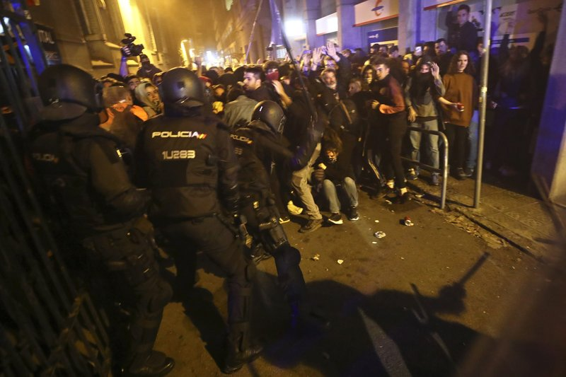 Policemen in riot gear charge against protestors in Barcelona, Spain, Tuesday, Oct. 15, 2019. Spain's Supreme Court on Monday convicted 12 former Catalan politicians and activists for their roles in a secession bid in 2017, a ruling that immediately inflamed independence supporters in the wealthy northeastern region. (AP Photo/Emilio Morenatti)