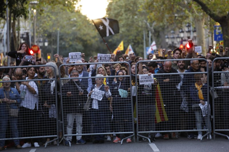 Protestors gather outside the Spanish Government Office in Barcelona, Spain, Tuesday, Oct. 15, 2019. Spain's Supreme Court on Monday convicted 12 former Catalan politicians and activists for their roles in a secession bid in 2017, a ruling that immediately inflamed independence supporters in the wealthy northeastern region. (AP Photo/Bernat Armange)