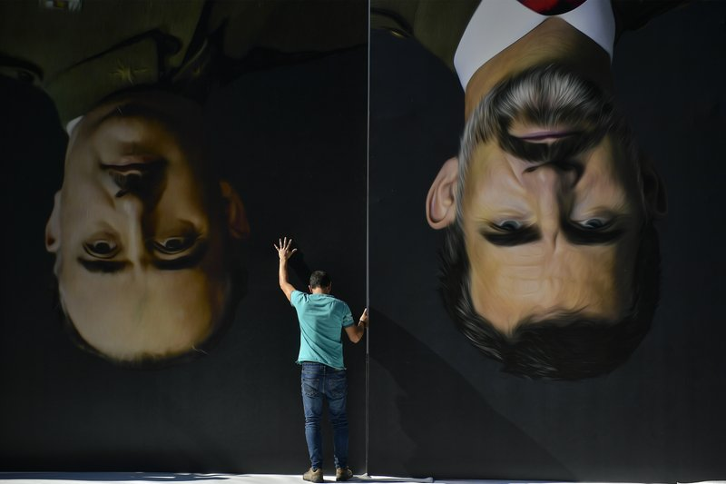 A man sets up upside down giant paintings of late Spanish dictator Francisco Franco, left, and Spanish King Felipe VI ahead of a protest by Basque pro-independence activists in support of Catalonia's independence movement following Spain's conviction of Catalan separatist leaders, in Bilbao, northern Spain, Tuesday, Oct. 15, 2019. Spain's Supreme Court on Monday sentenced 12 prominent former Catalan politicians and activists of illegally promoting the Catalonia region's independence. (AP Photo/Alvaro Barrientos)