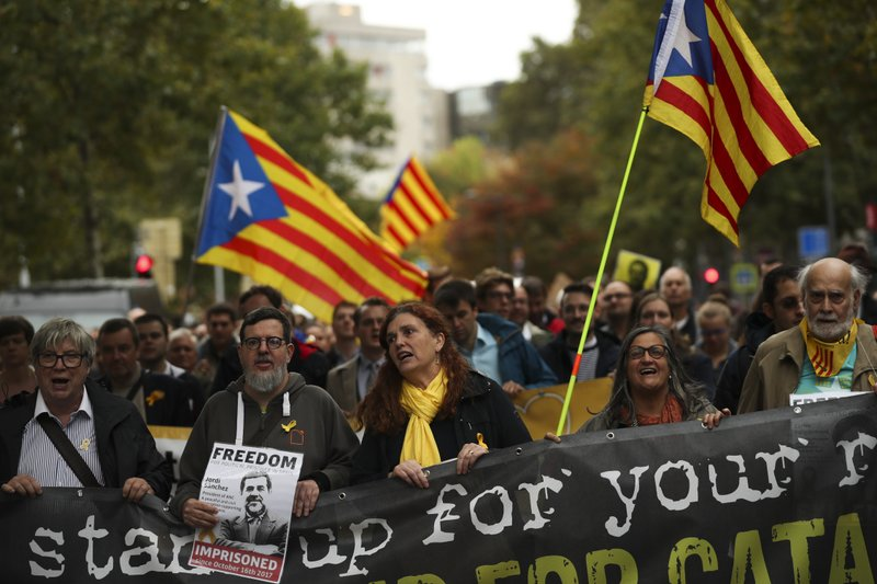 People, waving Estelada pro Catalonia independence flags, march during a protest in Brussels, Tuesday, Oct. 15, 2019. New disruptions to Catalonia's transportation network on Tuesday followed a night of clashes between activists and police over the conviction of separatist leaders, as Spanish authorities announced an investigation into the group organizing the protests. (AP Photo/Francisco Seco)