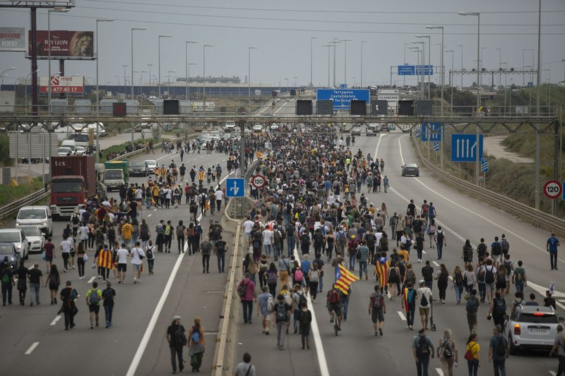 In this Monday, Oct. 14, 2019 photo, pro-independence protesters march towards El Prat airport, outskirts of Barcelona, Spain. Riot police engaged in a running battle with angry protesters outside Barcelona's airport Monday after Spain's Supreme Court convicted 12 separatist leaders of illegally promoting the wealthy Catalonia region's independence and sentenced nine of them to prison. (AP Photo/Joan Mateu)