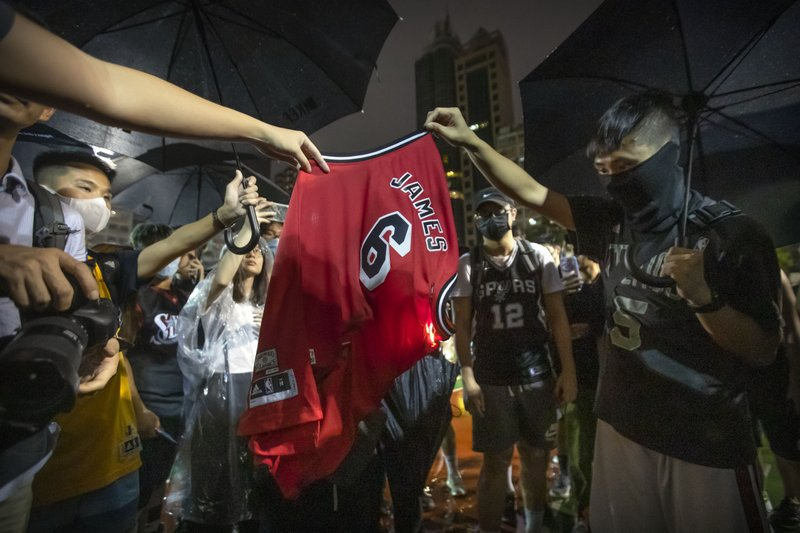 Demonstrators set a Lebron James jersey on fire during a rally at the Southorn Playground in Hong Kong, Tuesday, Oct. 15, 2019. Protesters in Hong Kong have thrown basketballs at a photo of LeBron James and chanted their anger about comments the Los Angeles Lakers star made about free speech during a rally in support of NBA commissioner Adam Silver and Houston Rockets general manager Daryl Morey, whose tweet in support of the Hong Kong protests touched off a firestorm of controversy in China. (AP Photo/Mark Schiefelbein)