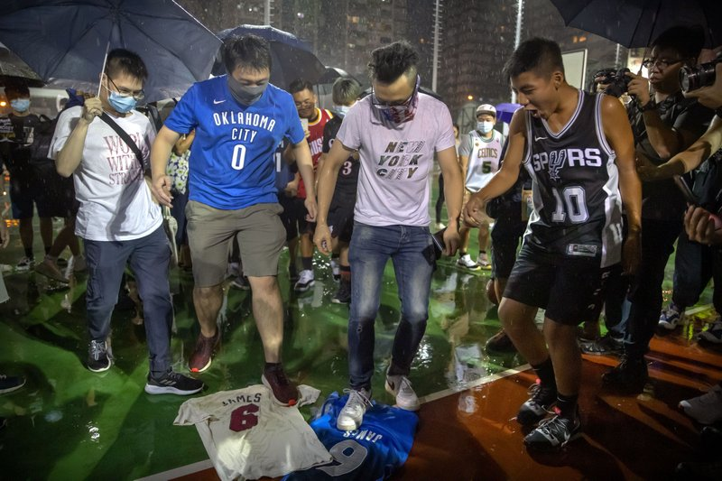 Demonstrators stamp on Lebron James jerseys during a rally at the Southorn Playground in Hong Kong, Tuesday, Oct. 15, 2019. Protesters in Hong Kong have thrown basketballs at a photo of LeBron James and chanted their anger about comments the Los Angeles Lakers star made about free speech during a rally in support of NBA commissioner Adam Silver and Houston Rockets general manager Daryl Morey, whose tweet in support of the Hong Kong protests touched off a firestorm of controversy in China. (AP Photo/Mark Schiefelbein)