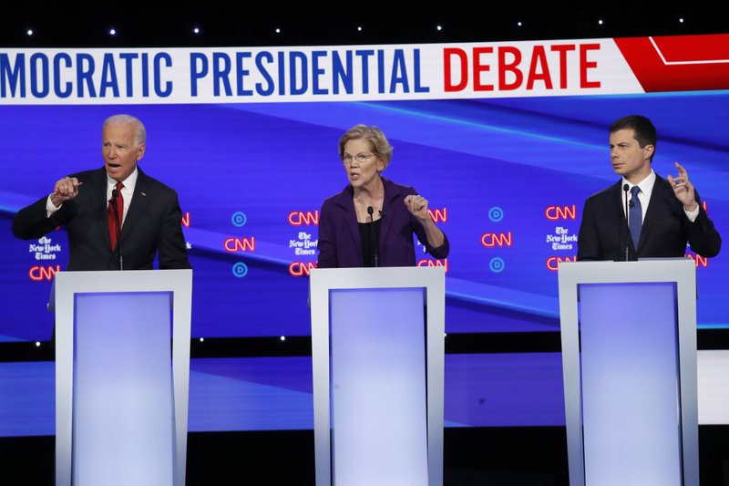 Democratic presidential candidate former Vice President Joe Biden, left, Sen. Elizabeth Warren, D-Mass., center and South Bend Mayor Pete Buttigieg speak during a Democratic presidential primary debate hosted by CNN/New York Times at Otterbein University, Tuesday, Oct. 15, 2019, in Westerville, Ohio. (AP Photo/John Minchillo)