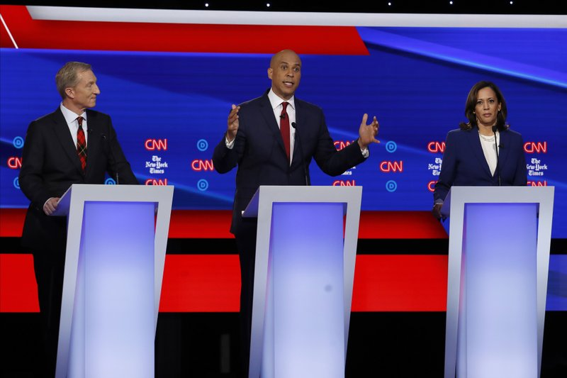 Democratic presidential candidate businessman Tom Steyer, left, Sen. Cory Booker, D-N.J., center, and Sen. Kamala Harris, D-Calif., participate in a Democratic presidential primary debate hosted by CNN/New York Times at Otterbein University, Tuesday, Oct. 15, 2019, in Westerville, Ohio. (AP Photo/John Minchillo)