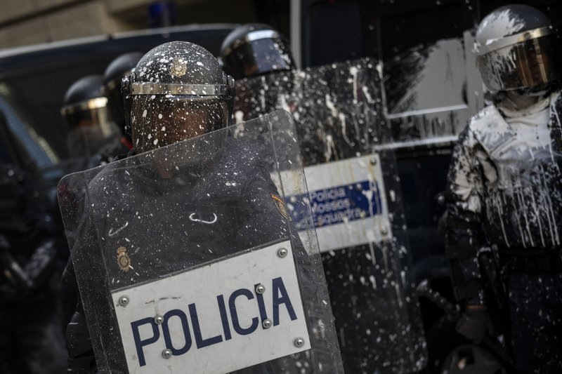 Catalan regional police covered in paint trhown by pro-independence demonstrators in Barcelona, Spain, Friday, Oct. 18, 2019. Various flights into and out of the region are cancelled Friday due to a general strike called by pro-independence unions and five marches of tens of thousands from inland towns are expected converge in Barcelona's center on Friday afternoon for a mass protest with students to and workers who are on strike. (AP Photo/Bernat Armangue)