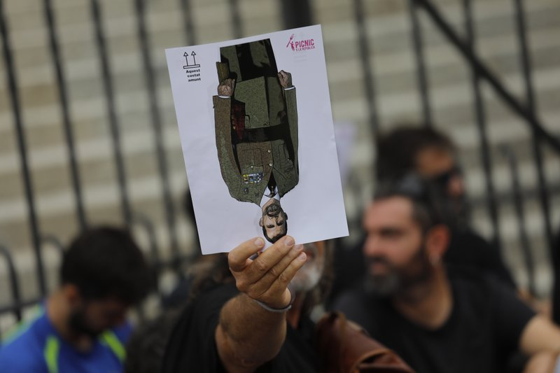 A protester holds a portrait of Spain's King Felipe upside down during a pro-independence gathering on the fifth day of protests over the conviction of a dozen Catalan independence leaders in Barcelona, Spain, Friday, Oct. 18, 2019. Various flights into and out of the region are cancelled Friday due to a general strike called by pro-independence unions and five marches of tens of thousands from inland towns are expected converge in Barcelona's center on Friday afternoon for a mass protest with students to and workers who are on strike. (AP Photo/Bernat Armangue)